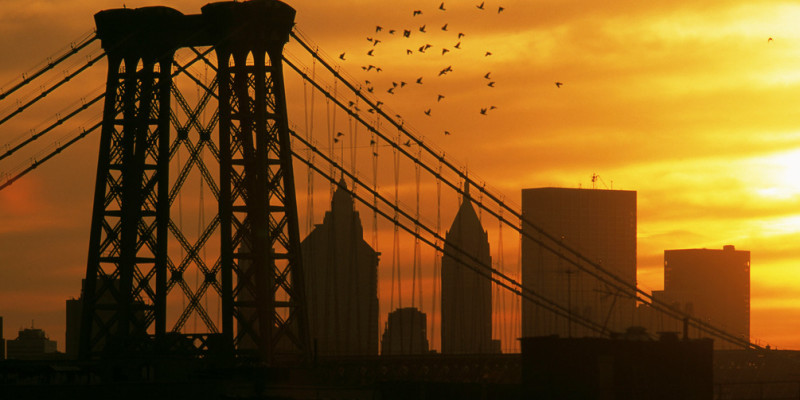 Williamsburg, Brooklyn, New York, 2000. A flock of pigeons flies above the Williamsburg Bridge at sunset. | photo by Thomas Hoepker