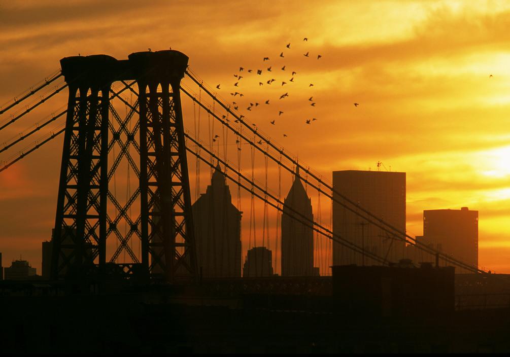 Williamsburg, Brooklyn, New York, 2000. A flock of pigeons flies above the Williamsburg Bridge at sunset. | photo by Thomas Hoepker